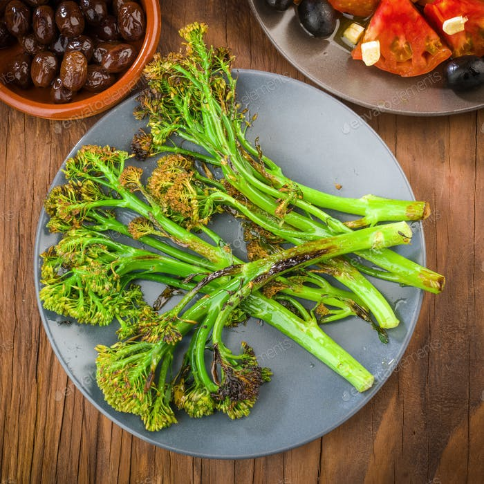 dish with tender shoots of broccoli grilled and tomato salad