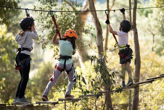 Determined kids crossing zip line
