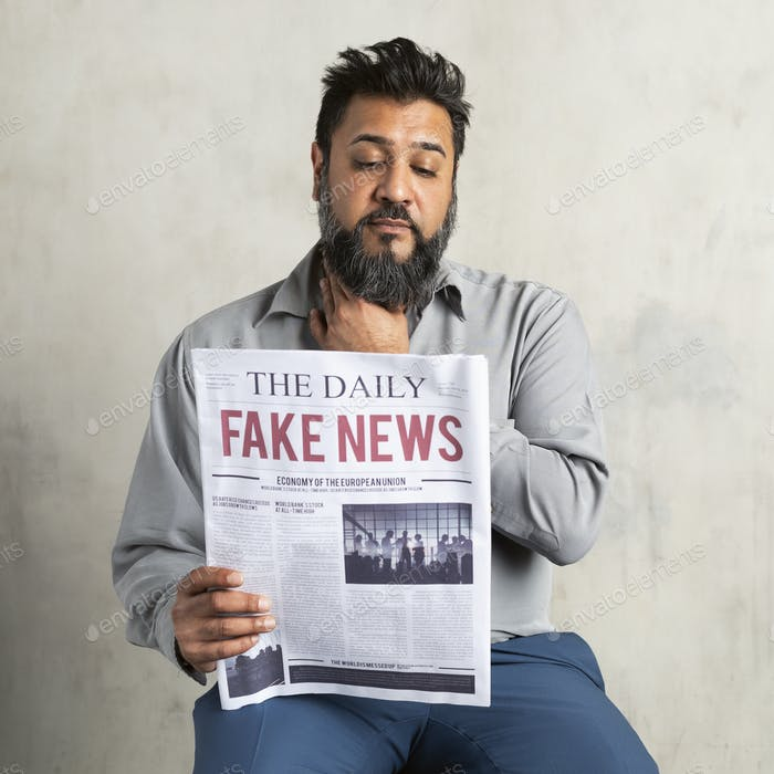 Doubtful Indian man reading the newspaper with fake news