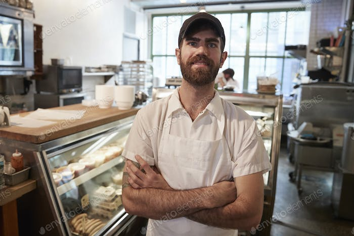 Young bearded butcher smiling to camera in his shop