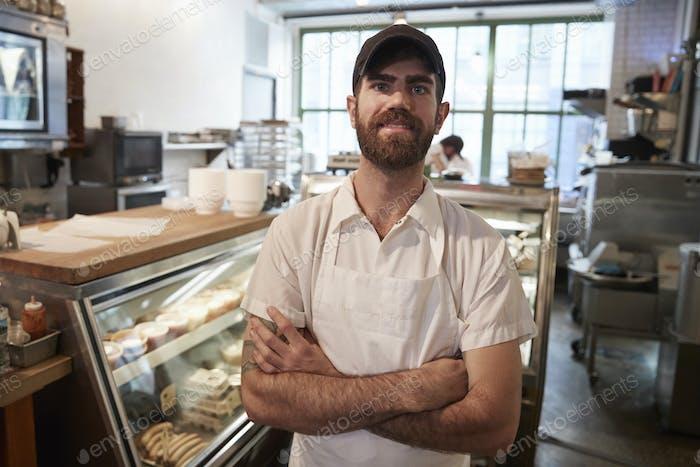 Junger bärtiger Metzger lächelnd zur Kamera in seinem Geschäft
