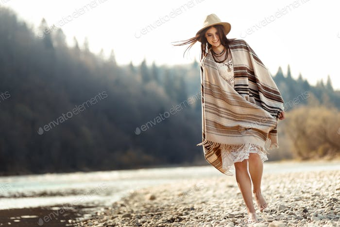 beautiful woman hipster walking on river beach in mountains