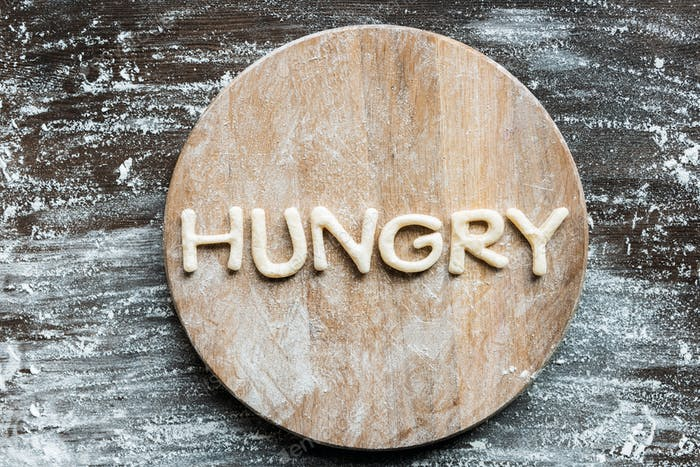 top view of word hungry made from cookie dough with flour on wooden cutting board