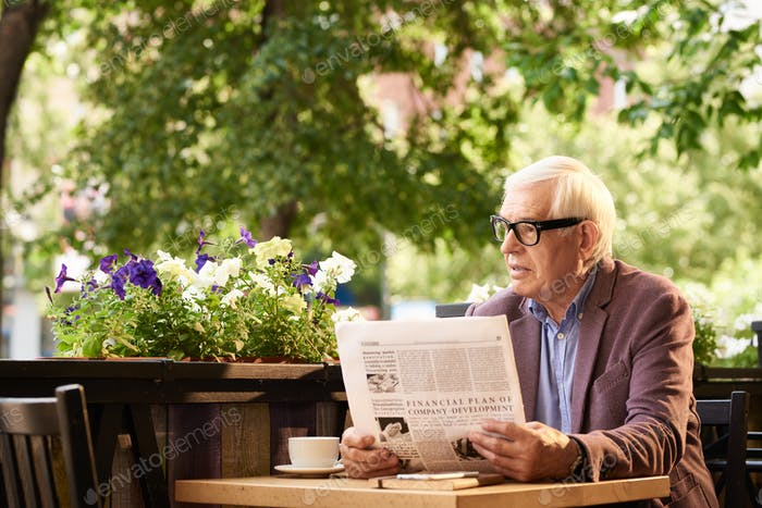 Modern Senior Man Reading Newspaper in Outdoor Cafe