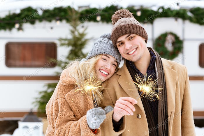 Smiling Romantic Couple In Knitted Hats Posing With Sparklers At Winter Camping