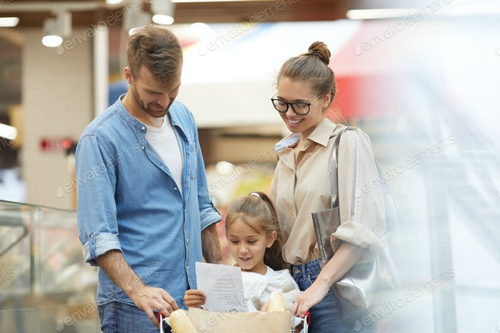 Happy Young Family Shopping in Supermarket