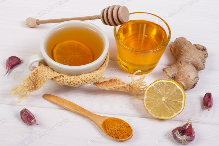 Cup of tea with lemon and ingredients for preparation warming beverage for winter evening