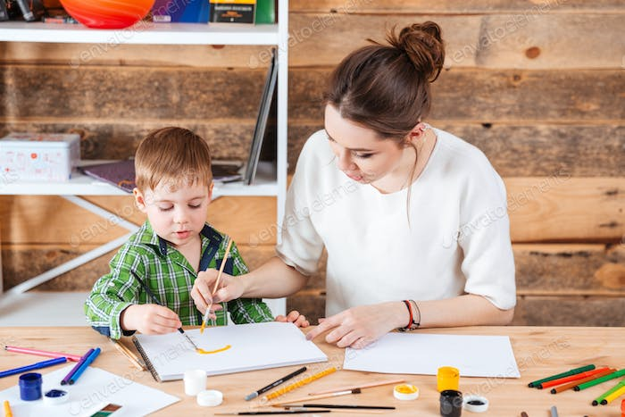 Mother and little son painting together in art school