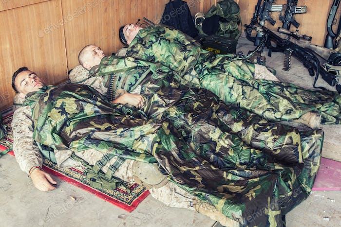 Tired soldiers sleeping on floor at temporary base