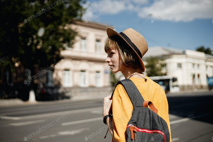 Young girl with headphones in a yellow t-shirt and a straw hat crossing the road with a backpack in