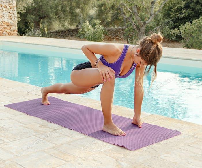 Junge Frau üben Eidechse Yoga Pose in der Nähe eines Pools