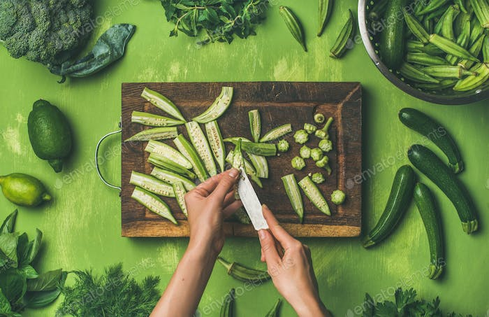 Woman hands cutting green vegetables and greens, top view