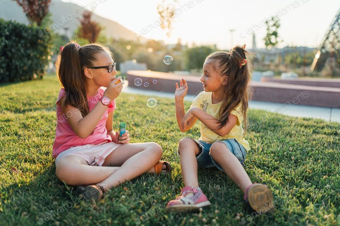 Two girls are sitting on the grass and blowing bubbles