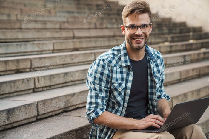 Young smiling man sitting on steps