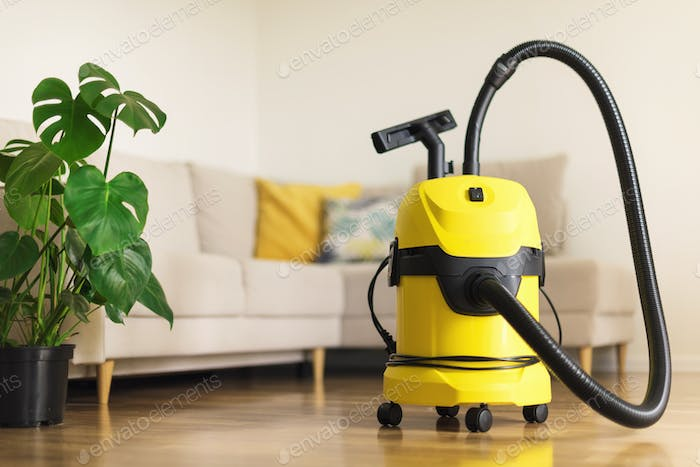Yellow modern vacuum cleaner in living room. Copy space. Flat clean vacuuming concept. Green