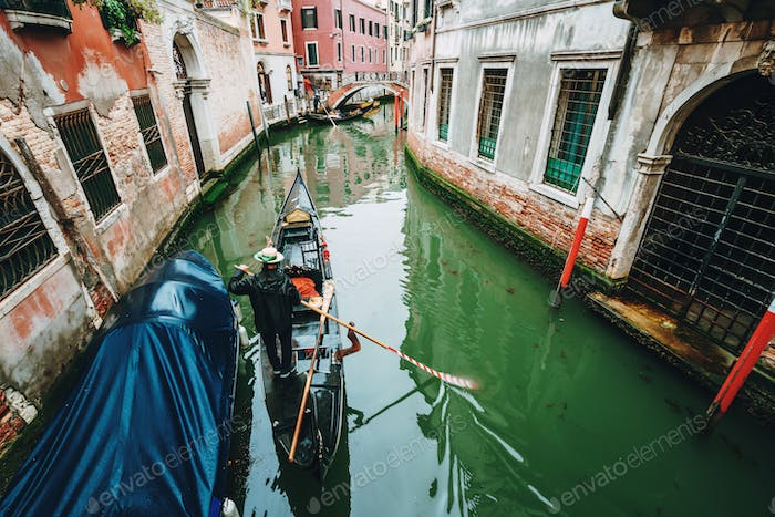 Venice Italy. Narrow canal with Gondola and old typical facade houses