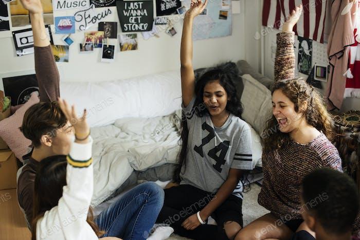 Gruppe von Teenagern in einem Schlafzimmer Arme erhöht Community und Temwork Konzept