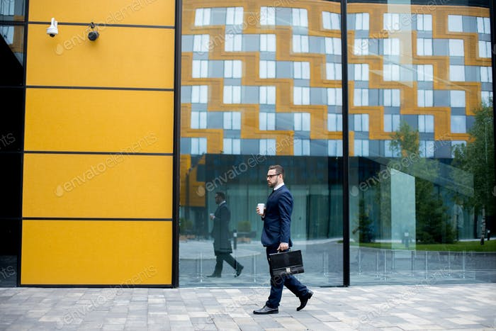 Man holding cup of hot drink and moving near office building