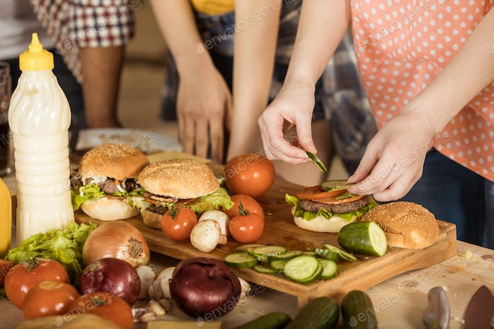 cropped shot of woman preparing tasty hamburgers for friends on kitchen board
