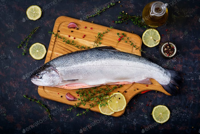 Fresh raw salmon red fish on a dark background. Flat lay. Top view