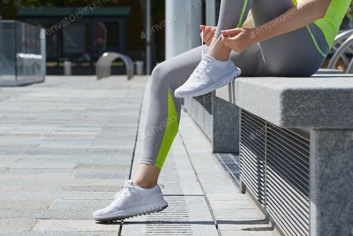 Frau binden Schnürsenkel vor dem Laufen im freien in der Stadt