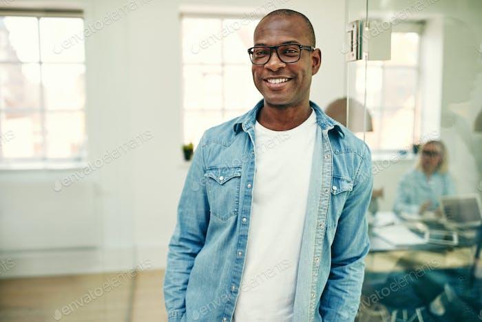 Lächelnd junge afrikanische Geschäftsmann stehend in einem modernen Büro
