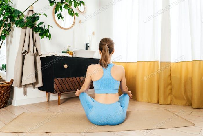 Young woman practicing yoga indoor. Morning ritual.