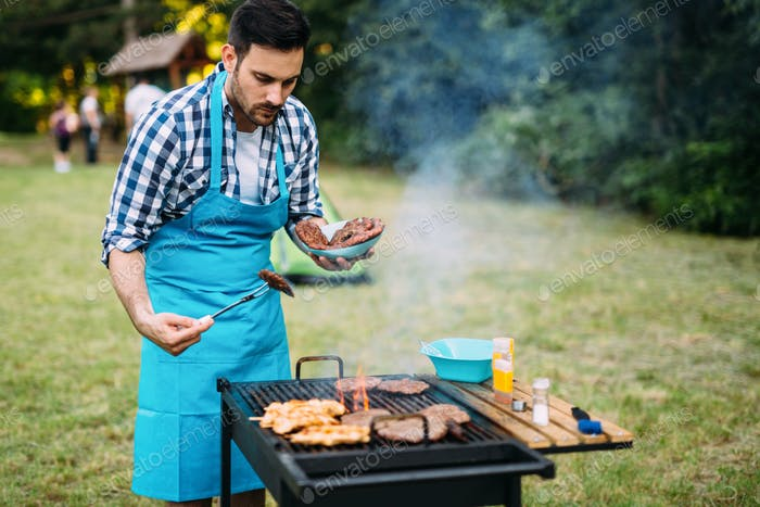 Happy male preparing bbq meat
