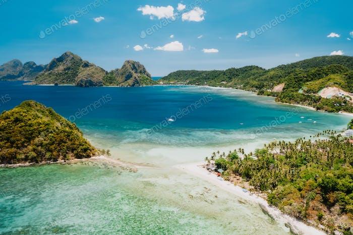 Aerial drone view of Las Cabanas sunny beach in El Nido, Palawan