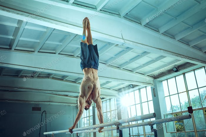 The sportsman during difficult exercise, sports gymnastics