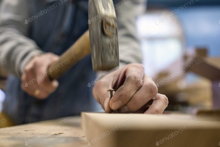 Close up of hammering a nail into wooden board