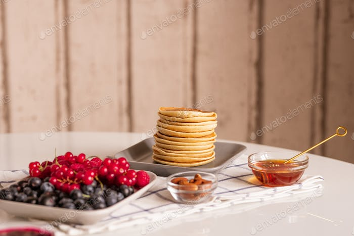 Stack of small homemade pancakes, fresh ripe red currant and blackberries