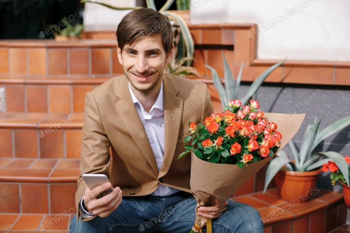 Smiling man texting while looking at the phone in his hands