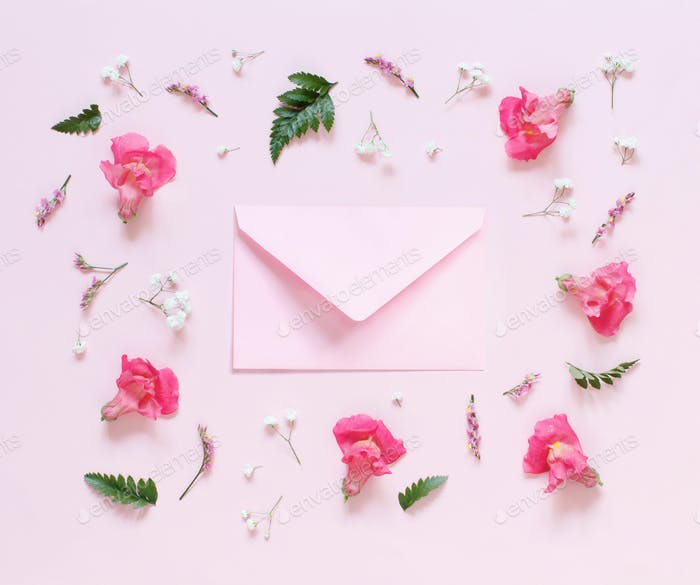 Flowers and pink envelope on a light pink background