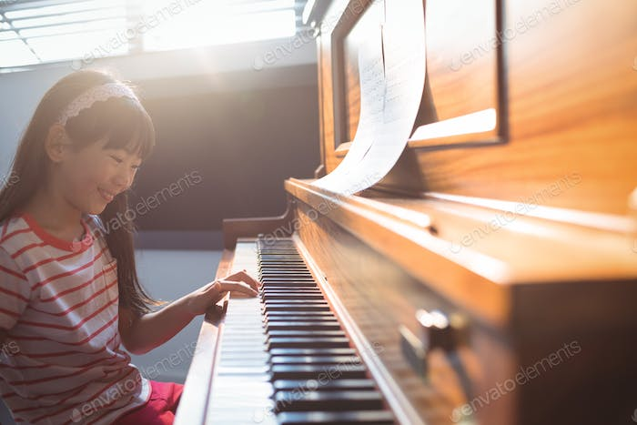 Smiling girl practicing piano in class