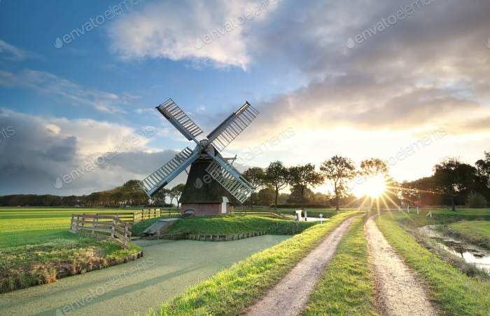windmill, rural road and river at sunrise