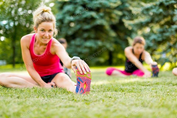 junge Frau stetching vor einem joggen