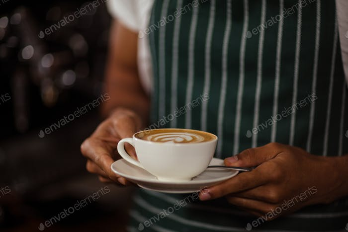 Close up of barista holding cappuccino in the bar