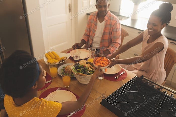 Happy African American family having food at dining table in their comfortable home