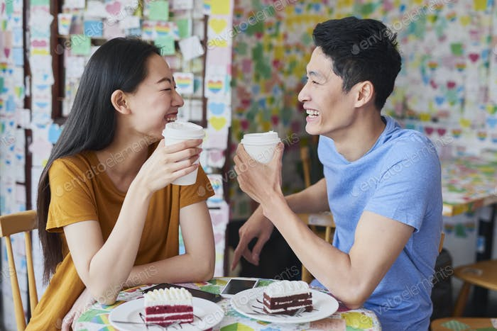 Cheerful couple have interesting discussion in a cafe