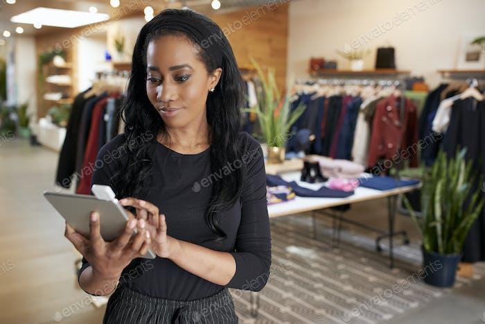 Junge schwarze Frau mit Tablet-Computer in einem Bekleidungsgeschäft