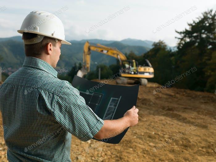 male engineer reading blueprint