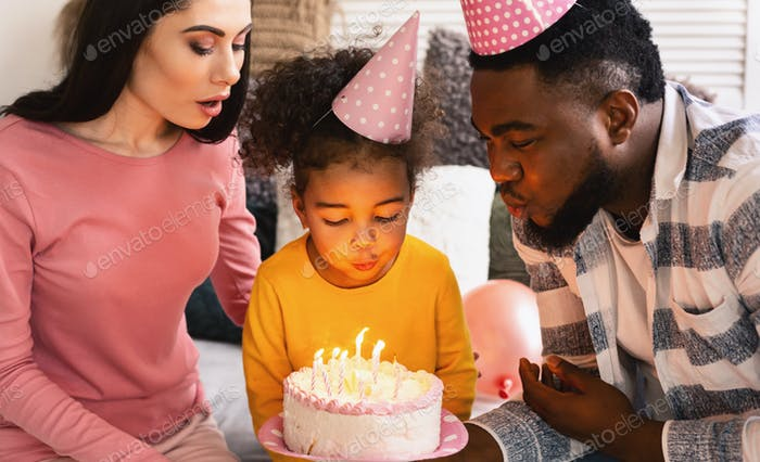 Childs birthday International parents help blow out candles