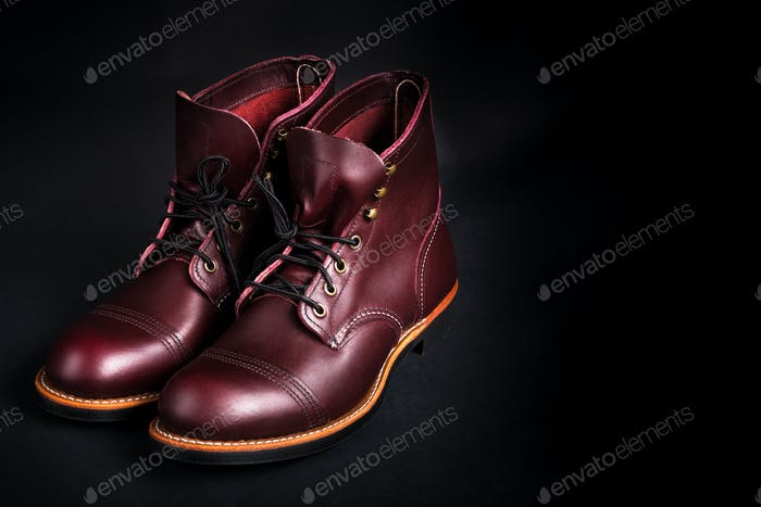 High boots. Fashionable mens leather brown shoes on black background. Back view. Copy space.
