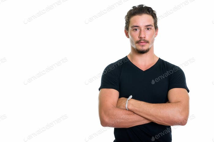 Studio shot of young handsome man with arms crossed isolated aga