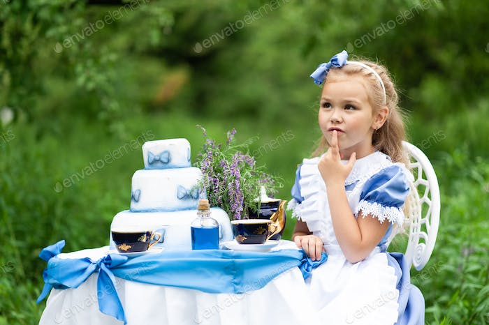 """A little cute girl in the costume """"Alice from Wonderland"""" holds a tea party at her magic table."""