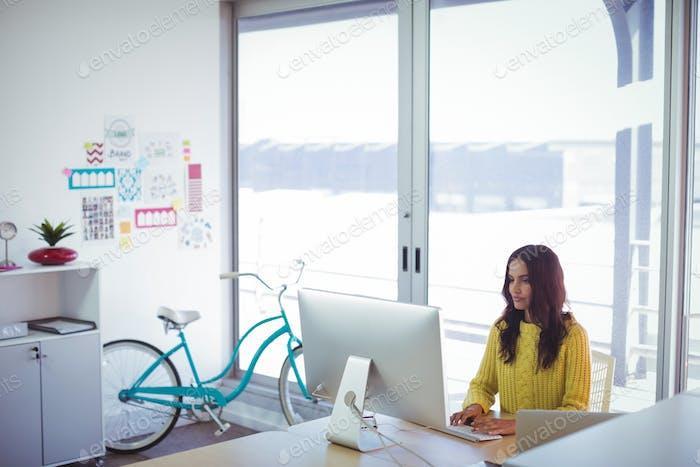 Female graphic designer using computer in office