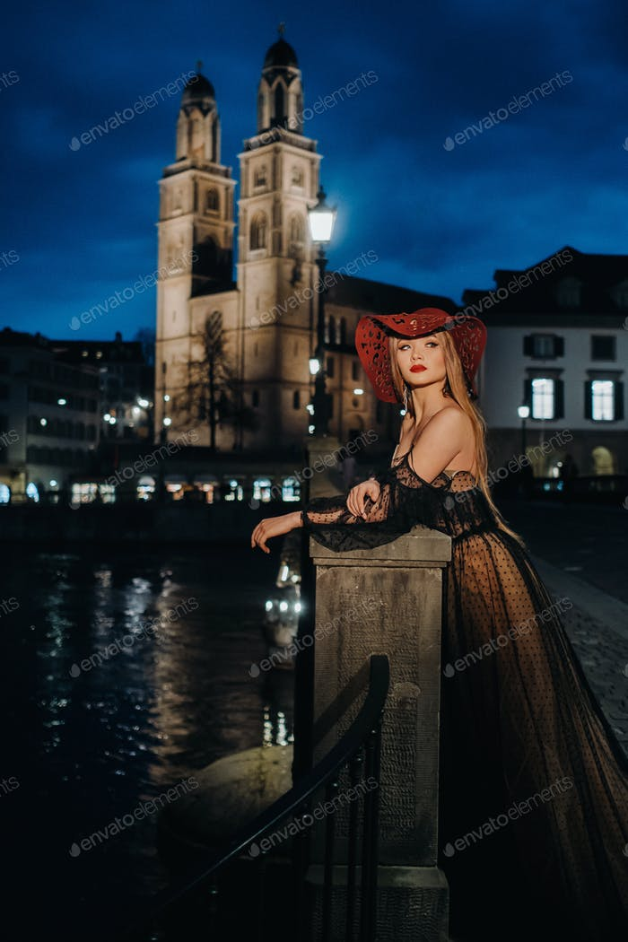 A stylish bride in a black wedding dress and red hat poses at night in the old city of Zurich