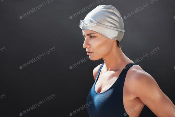 Fit young woman in swimming costume looking away
