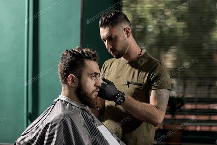 Brutal man sits at a barber shop. Barber makes a trim